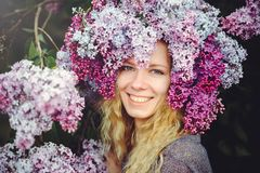 Outdoor fashion photo of a beautiful young blue-eyed woman. Spring color. beautiful blonde girl in lilac flowers. Perfume with a s. Cent of flowers. Perfumes and stock image