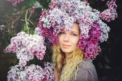 Outdoor fashion photo of a beautiful young blue-eyed woman. Spring color. beautiful blonde girl in lilac flowers. Perfume with a s. Cent of flowers. Perfumes and stock photo