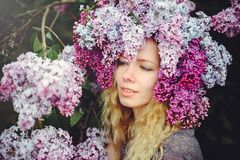 Outdoor fashion photo of a beautiful young blue-eyed woman. Spring color. beautiful blonde girl in lilac flowers. Perfume with a s. Cent of flowers. Perfumes and royalty free stock photography