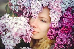 Outdoor fashion photo of a beautiful young blue-eyed woman. Spring color. beautiful blonde girl in lilac flowers. Perfume with a s. Cent of flowers. Perfumes and stock photos