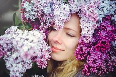 Outdoor fashion photo of a beautiful young blue-eyed woman. Spring color. beautiful blonde girl in lilac flowers. Perfume with a s. Cent of flowers. Perfumes and stock photography