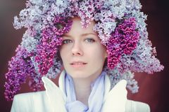 Outdoor fashion photo of a beautiful young blue-eyed woman. Spring color. beautiful blonde girl in lilac flowers. Perfume with a s. Cent of flowers. Perfumes and stock images
