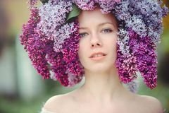Outdoor fashion photo of a beautiful young blue-eyed woman. Spring color. beautiful blonde girl in lilac flowers. Perfume with a s. Cent of flowers. Perfumes and royalty free stock images