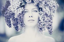 Outdoor fashion photo of a beautiful young blue-eyed woman. Spring color. beautiful blonde girl in lilac flowers. Perfume with a s. Cent of flowers. Perfumes and royalty free stock image