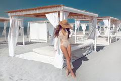 Outdoor fashion photo of Sexy bikini model in straw hat on tropi. Cal beach. Beautriful brunette sun tanning posing on white sand by beach bed. Exotic Resort Royalty Free Stock Photography
