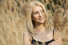 Outdoor fashion photo of young beautiful lady in autumn landscape with dry flowers Royalty Free Stock Photo