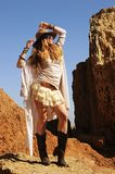 Outdoor fashion photo of young happy woman in hat, standigg against rocks, hands up stock images
