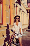 Outdoor fashion portrait of attractive blonde young woman on a v. Intage bike Royalty Free Stock Photography