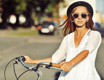 Outdoor fashion portrait of a beautiful blonde with bike Royalty Free Stock Image