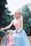 Outdoor fashion portrait of a beautiful blonde girl cycling in the park Stock Image