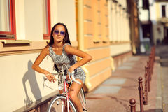 Outdoor fashion portrait of a beautiful brunette with bike Royalty Free Stock Photos