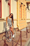 Outdoor fashion portrait of a beautiful brunette with bike Stock Photos
