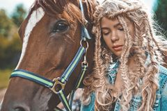 Beautiful young girl with brown horse. Outdoor fashion portrait of beautiful young girl with brown horse. Hippie style. Summer vibes. Autumn season Royalty Free Stock Photography