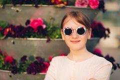 Outdoor fashion portrait of cute preteen girl. Portrait of cute little girl wearing vintage sunglasses, posing outdoors Royalty Free Stock Images