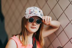 Outdoor fashion portrait of cute preteen girl. Outdoor portrait of cute little preteen girl wearing fashion cap and sunglasses Royalty Free Stock Image