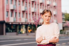 Outdoor fashion portrait of cute preteen girl. Street style portrait of cute little girl wearing beige blouse and pink watch, fashion for children Royalty Free Stock Image
