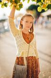 Outdoor fashion portrait of cute preteen girl. Wearing brown dress and yellow knitted jacket Stock Photography