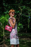 Outdoor fashion portrait of glamour sensual young stylish lady in sunglasses with luxury handmade snakeskin python bag Stock Photos