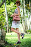 Outdoor fashion portrait of glamour sensual young stylish lady in sunglasses with luxury handmade snakeskin python bag. Python handbag. Sunny day, green plants Stock Photography