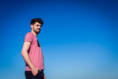 Outdoor fashion portrait of handsome man posing. In nice sunny day, beautiful view on blue sky stock image
