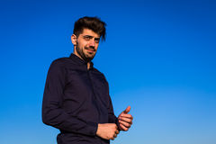 Outdoor fashion portrait of handsome man posing. In nice sunny day, beautiful view on blue sky royalty free stock photos