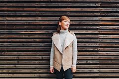 Outdoor fashion portrait of pretty little preteen girl. Of 10 years old, wearing beige vest, posing against brown wooden background Stock Photography