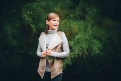 Outdoor fashion portrait of pretty little preteen girl. Of 10 years old, wearing beige vest, posing against green tree Stock Images