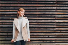 Outdoor fashion portrait of pretty little preteen girl. Of 10 years old, wearing beige vest, posing against brown wooden background Stock Image