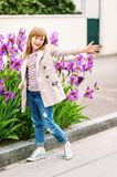 Little girl portrait. Outdoor fashion portrait of 9-10 year old hipster girl wearing stylish trench coat Stock Photo