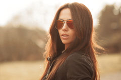 Outdoor fashion portrait of young brunette woman in sunglasses Stock Photography