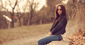 Outdoor fashion portrait of young brunette woman in sunglasses. Royalty Free Stock Image