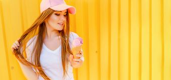Outdoor fashion portrait of young hipster girl with ice-cream on yellow wall background royalty free stock images