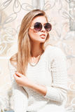 Outdoor fashion portrait of young pretty woman with round sunglasses in summer sunny day on street. royalty free stock images