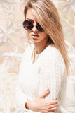 Outdoor fashion portrait of young pretty woman with round sunglasses in summer sunny day on street. stock photography