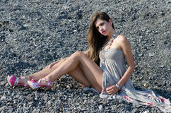 Outdoor fashion shoot sitting on rocky ground. Outdoor fashion shoot wearing long dress and heels sitting on rocky ground, full length and horizontal photo stock photos