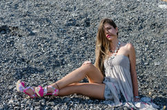 Outdoor fashion shoot sitting on rocky ground. Outdoor fashion shoot wearing long dress and heels sitting on rocky ground, full length and horizontal photo royalty free stock images