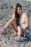 Outdoor fashion shoot sitting on rocky ground. Outdoor fashion shoot wearing long dress and heels sitting on rocky ground, full length and vertical photo royalty free stock photography