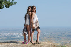 Outdoor fashion shoot of two women. Both wearing long dresses. Photo taken place on hill, small village and field as background, full length and horizontal stock photos
