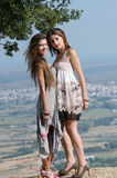 Outdoor fashion shoot of two women. Both wearing long dresses. Photo taken place on hill, small village and field as background, full length and vertical photo stock image