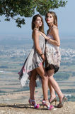 Outdoor fashion shoot of two women. Both wearing long dresses. Photo taken place on hill, small village and field as background, full length and vertical photo royalty free stock images
