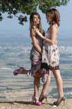Outdoor fashion shoot of two women. Both wearing long dresses. Photo taken place on hill, small village and field as background, full length and vertical photo stock photography