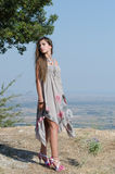 Outdoor fashion shoot. Wearing long dress and heels. Photo taken place on hill, field as background, full length and vertical photo stock photography