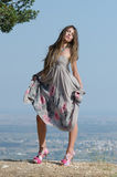 Outdoor fashion shoot. Wearing long dress and heels. Wind blow the dress. Photo taken place on hill, small village and field as background, full length and stock photography
