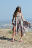 Outdoor fashion shoot. Wearing long dress and heels. Wind blow the dress. Photo taken place on hill, small village and field as background, full length and stock image