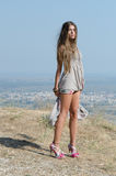 Outdoor fashion shoot. Wearing long dress, holding her clothe and reveal her long legs. Photo taken place on hill, small village and field as background, full stock image