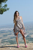 Outdoor fashion shoot. Wearing long dress, holding her clothe and reveal her long legs. Photo taken place on hill, small village and field as background, full stock photo
