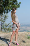 Outdoor fashion shoot. Wearing long dress, holding her clothe and reveal her long legs. Photo taken place on hill, small village and field as background, full stock photography