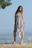 Outdoor fashion shoot. Wearing long dress. Photo taken place on hill, small village and field as background, full length and vertical photo stock photos