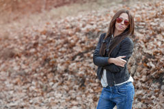 Outdoor fashion toned colors portrait of young woman in jea Stock Image