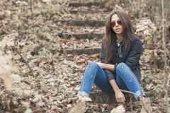Outdoor fashion toned colors portrait of young sexy woman in jea Stock Image